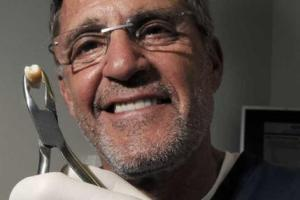 Dentist Dr. Jeffrey Blum holds up a molar similar to the one that would be sent to a cryogenics lab in New York City to be frozen and stored.